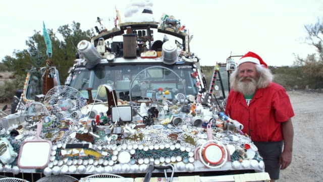 MS, Portrait of baby boomer man wearing santa's hat standing by  adorned truck, Niland, California, USA