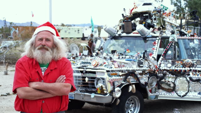 MS, Portrait of baby boomer man wearing santa's hat standing in front of adorned truck, Niland, California, USA