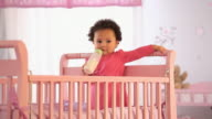 MS Portrait of baby girl (19-23 months) drinking from baby bottle, standing in crib / Richmond, Virginia, USA