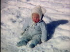 1963 MS Portrait of baby girl wearing snowsuit sitting on snow, Vermont, USA
