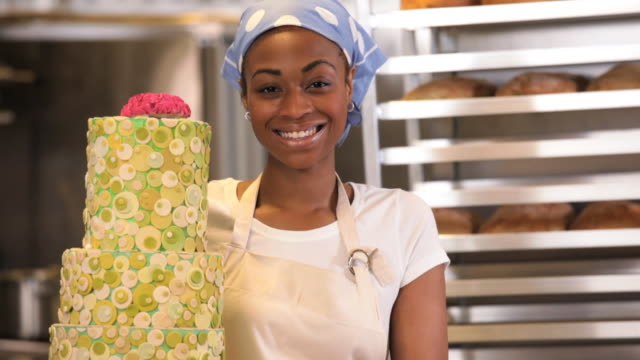 MS TU Portrait of Baker in Commercial Kitchen Holding Large Cake / Richmond, Virginia, USA