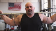 MS Portrait of bodybuilder in gym with US flag in background, Middletown, Connecticut, USA