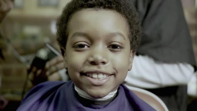 CU TU Portrait of boy (8-9) having haircut done at barbershop, Brooklyn, New York City, New York State, USA