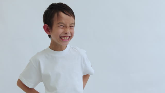 MS Portrait of boy (8-9) making funny face in studio / Shibuya, Tokyo, Japan