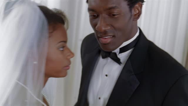 Portrait of bride and groom / tilt down to couple holding hands / tilt up