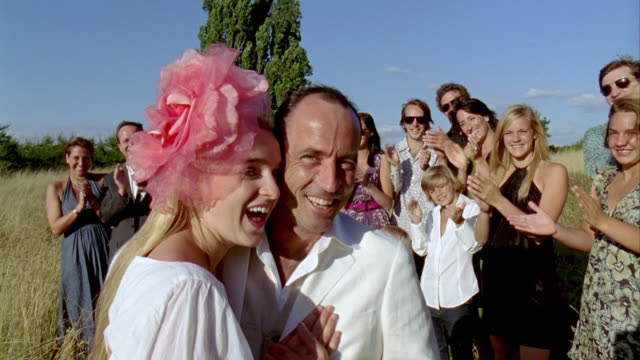 CU, Portrait of bride and groom, wedding guests clapping hands in background, Saint Ferme, Gironde, France