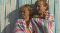 Portrait of brother and sister on beach wrapped in beach towel