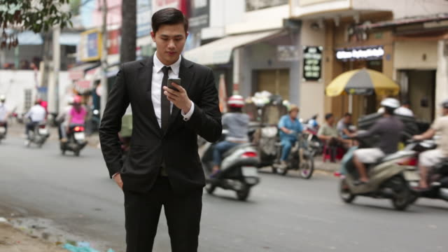 WS Portrait of businessman in suit texting and using mobile phone, in front of busy street of motor scooters
