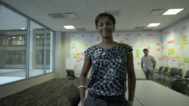 ZI MS Portrait of businesswoman in creative conference room, man in background, Chicago, Illinois, USA