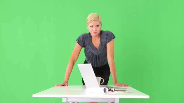 Portrait of businesswoman leaning on desk with laptop