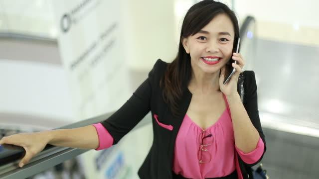 portrait of businesswoman using smart phone on escalator
