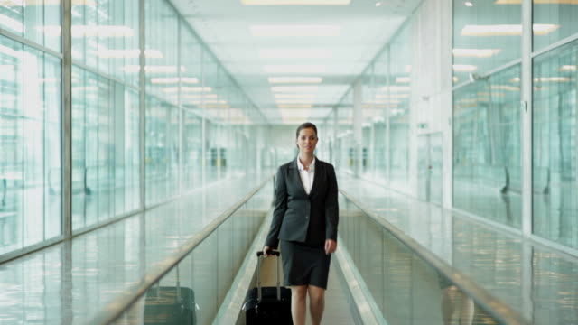 WS MS Portrait of businesswoman with case in airport on moving walkway / Toulouse, Haute-Garonne, France