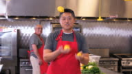 MS Portrait of Chef in Commercial Kitchen Speaking to Camera, While Juggling Lemons / Richmond, Virginia, USA