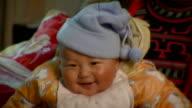CU Portrait of Chinese  baby sitting on mothers laps, near Taizhou, Jiangsu, China