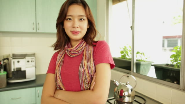 MS Portrait of Chinese woman in kitchen with arms folded