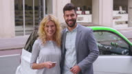 SLO MO Portrait of couple charging car at EV station