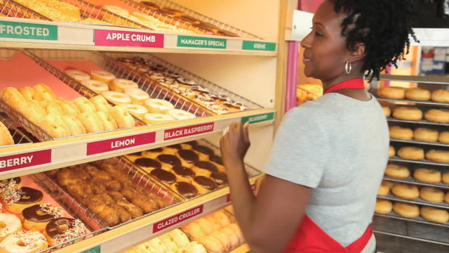 MS Portrait of donut shop owner placing tray of donuts on shelf and turning to smile at camera/ Richmond, Virginia, USA