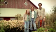 Portrait of family of organic farmers posing with basket of fresh produce in front of barn / son frowning then smiling again
