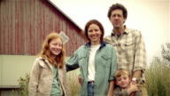 Portrait of family on family farm / boy frowning at first then smiling