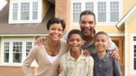 MS portrait of family with 2 children in front of suburban home