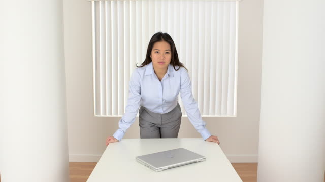 Portrait of female Asian businesswoman leaning on table