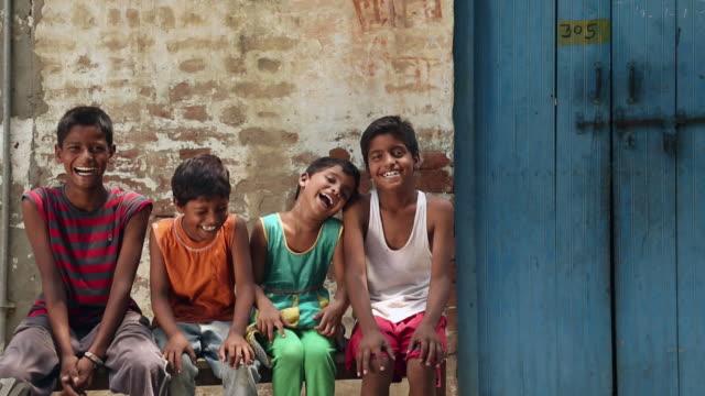 Portrait of four kids smiling, Haryana, India