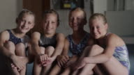 MS Portrait of four smiling girls (8-9, 10-11) in gym, Orem, Utah, USA