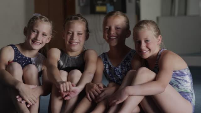 MS Portrait of four smiling girls (8-9, 10-11) in gym, Orem, Utah, USA