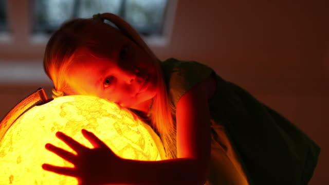 MS Portrait of girl (4-5) embracing illuminated globe / Brussels, Brabant, Belgium
