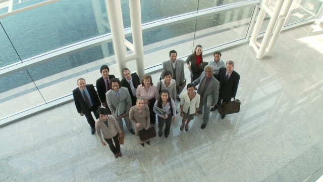 WS HA Portrait of group of business people rising hands, standing in lobby / Bangkok, Thailand