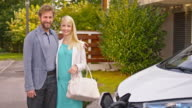 SLO MO Portrait of happy couple and their electric car