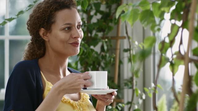 CU Portrait of happy woman drinking coffee / Edmonds, Washington, USA