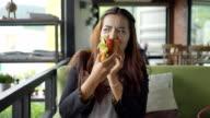 Ritratto di felice donna avere un panino alla caffetteria