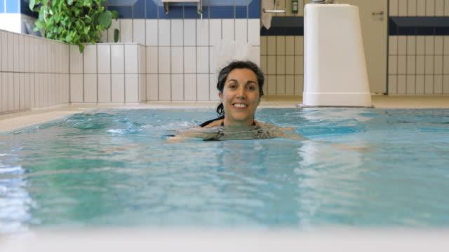 Portret van gelukkige vrouw zwemmen in zwembad op sportschool