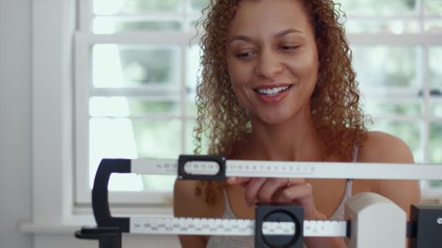 CU R/F Portrait of happy woman weighing herself on scale in bathroom / Edmonds, Washington, USA