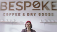 SLO MO. Portrait of hipster with mustache in local coffee shop.