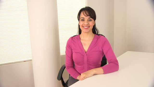 Portrait of Hispanic businesswoman at desk