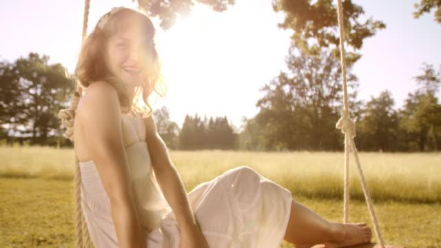 SLO MO portret van vrolijke vrouw op schommel in de zon