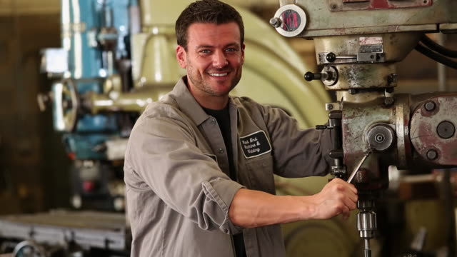MS Portrait of Machine Worker Standing at Drill Press in Machine Shop
