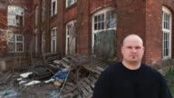 MS Portrait of man in front of deserted factory building, Middletown, Connecticut, USA
