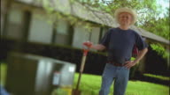 SLO MO MS R/F Portrait of man with cowboy hat and shovel standing in front yard next to ground transformer / Cedar Park, Texas, USA