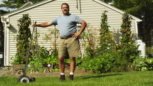 WS Portrait of man with lawn mower with vegetable garden and house in background, Manchester, Vermont, USA