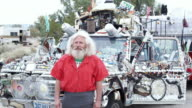 MS, Portrait of mature baby boomer man standing in front of adorned truck, Niland, California, USA