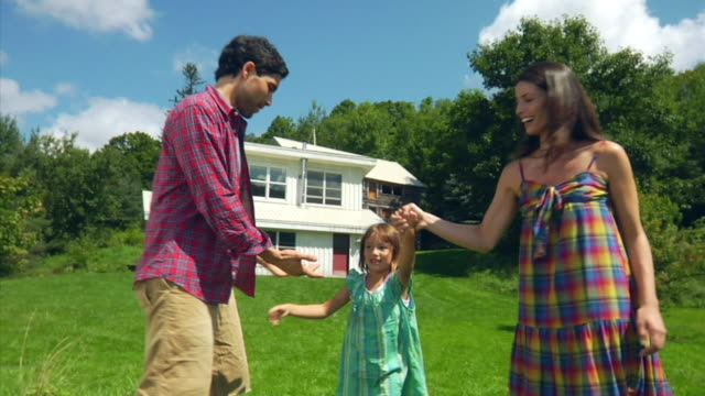 MS Portrait of mother and father holding hands with daughter (4-5), swinging, Bovina Center, New York, USA