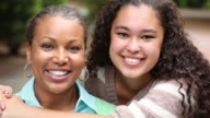 Portrait of mother and teenager daughter smiling.