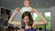 SLO MO MS Portrait of mother carrying baby boy (6-11 months) on shoulders and dancing / London, United Kingdom