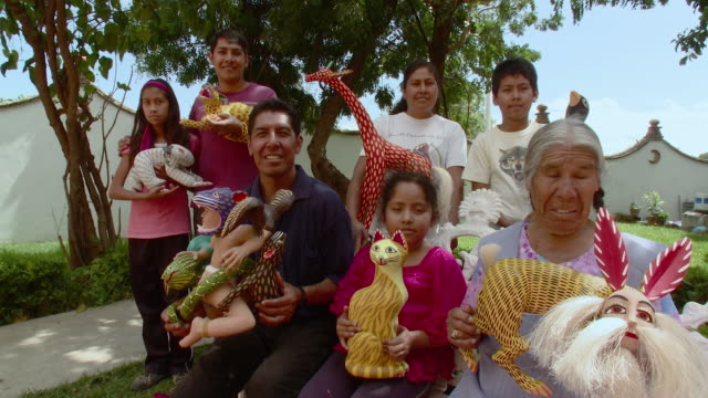 MS Portrait of multigenerational family holding alebrijes, brightly colored Mexican folk art sculptures of animals and fantastical creatures / Oaxaca, Mexico