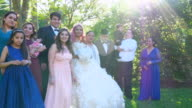 MS Portrait of multigenerational family standing in backyard with young woman dressed in quinceanera gown