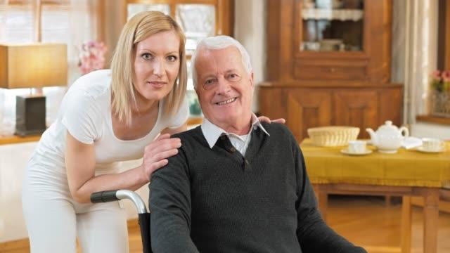 DS Portrait of nurse with senior man in wheelchair