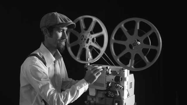 Portrait Of Old Fashioned Cinema Projectionist Starting New Film